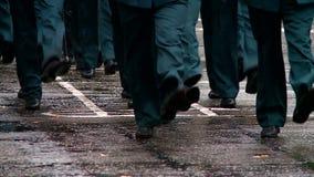 Militärt marschera på ståtar jordning i regnfoten i ramen stock video