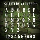 Militärt stencilalfabet på en kamouflage Royaltyfri Foto