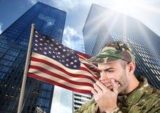 militair behandelend zijn mond tegen Amerikaanse vlag en skyscrappers Stock Afbeeldingen
