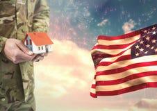 Militair die een klein huis dicht bij de Amerikaanse vlag houden stock foto