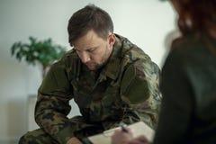 Militair die en aan zijn therapeut zitten spreken stock fotografie