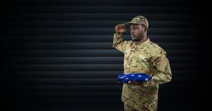 militair het groeten met de vlag van de V.S. in zijn hand Donkere achtergrond Royalty-vrije Stock Foto