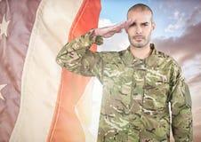 Militair het groeten tegen een fladderende Amerikaanse vlag Stock Foto's