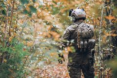 Militair in lichaamspantser en helmtribunes in het bos stock afbeelding