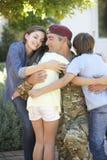 Militair Returning Home And door Familie wordt begroet die Stock Afbeelding