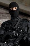 Militair in zwarte eenvormig met een kanon Stock Afbeelding