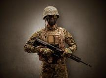 Militairagent in een donkere ruimte met wapens stock fotografie