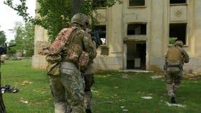 Militaire bewapende ploeg die op een opdracht zijn die elke anderen behandelen die terug in een verlaten gebouw binnengaan stock footage