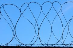 Militaire de Veiligheidsomheining met weerhaken Against Blue Sky van de Scheermesdraad stock foto