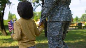 Militaire et garçon avec le drapeau national marchant ensemble en parc, avenir sûr clips vidéos
