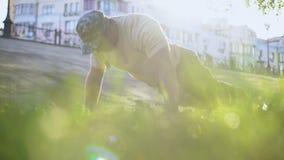 Militaire faisant des pousées extérieures, s'exerçant en parc de ville sur le coucher du soleil, discipline banque de vidéos