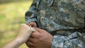Militaire man die verlovingsring op vrouwenhand zetten, paarhuwelijk, geloftebelofte stock footage