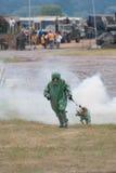 Militaire manager met hond in de uitrusting van de gasdefensie Stock Foto's