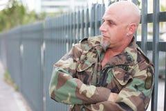 Militaire mens die op de omheining leunt Royalty-vrije Stock Afbeeldingen