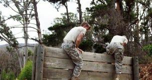 Militaire militairen die een houten muur beklimmen bij laarskamp 4k stock video