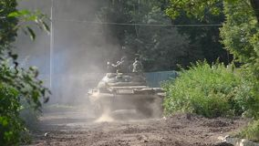 Militaire militairen die op oorlogstank zitten die zich op weg bij het schieten van waaier bewegen stock video