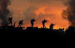 Militaire militairen in vernietigde stad in zonsondergang stock foto's