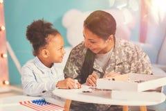 Militaire moeder en haar dochter die een puzzel doen stock foto's