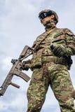 Militaire tenant l'arme automatique et la grenade à main image libre de droits