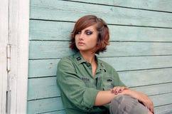 Militaire vrouwen die vóór houten muur zitten stock fotografie