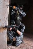 Militairen die in maskers het doel met kanonnen streven Stock Fotografie