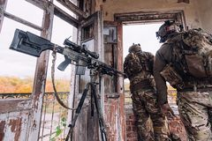 Militairen in militaire uniformen dichtbij een sluipschuttergeweer royalty-vrije stock foto