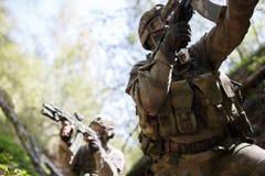 Militairen in oorlog bij hout Royalty-vrije Stock Afbeeldingen