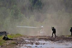 Militairen op een modderige grond met militaire helikopter op de achtergrond - leger en militaire technologiedemonstraties Stock Foto