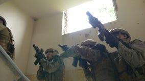 Militairen op opdracht om terroristenleider het stijgen aan parterre van een verlaten gebouw op zoek naar doel te doden stock footage