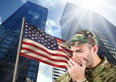 militaires couvrant sa bouche contre le drapeau américain et les skyscrappers Images stock