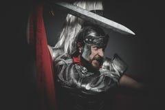 Militaires, légionnaire romain prétorien et manteau, armure et commutateur rouges Photo stock