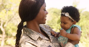 Soldier mother holding her daughter in a park Stock Footage