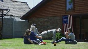 Militar con la familia en patio trasero almacen de metraje de vídeo