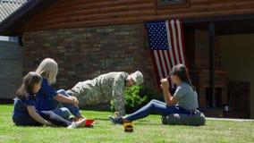 Militar con la familia en patio trasero fotos de archivo