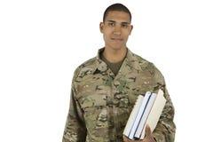Militar del afroamericano con los libros de escuela foto de archivo