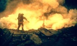 Militar entre el fuego y el humo en casa destruida foto de archivo