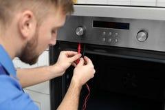 Militar profesional que repara el horno en cocina fotografía de archivo libre de regalías