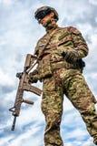 Militar que sostiene el rifle automático y la granada de mano Fotos de archivo