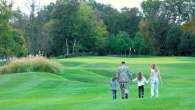 Militar y esposa que caminan y que juegan con las hijas, vista posterior almacen de metraje de vídeo