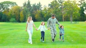 Militar y familia que caminan y que se divierten almacen de metraje de vídeo