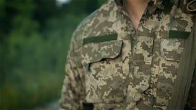 Militare che cammina attraverso la strada sabbiosa stock footage