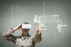 Militare nell'interfaccia commovente della cuffia avricolare di VR contro fondo verde con le interfacce Fotografia Stock
