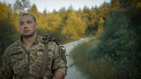 Militare sicuro che cammina attraverso la strada sabbiosa archivi video