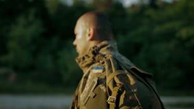 Militare sicuro che cammina attraverso la strada sabbiosa stock footage