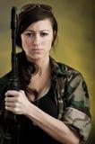 Militarisierte junge Frau mit Sturmgewehr Stockfoto