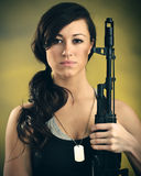 Militarized Young Woman WIth Assault Rifle. A young caucasian woman with an assault rifle royalty free stock photo