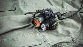 Militarna paracord bransoletka, taktyczna pochodnia i szkło, zdjęcie stock