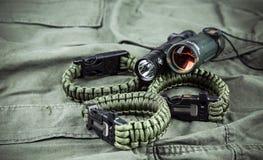 Militarna paracord bransoletka, taktyczna pochodnia i szkło, fotografia stock