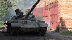 Militarny cysternowy jeżdżenie na drogowym zwolnionym tempie Wojenny zbiornik na bakground ceglanym domu zbiory