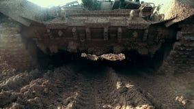 Militarny zbiornik z brudnymi gąsienicowymi śladami stoi na drodze pojazd pancerny zbiory